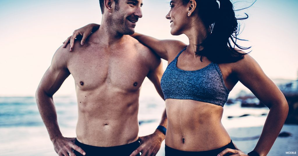 A couple on the beach after receiving a coolsculpting treatment.